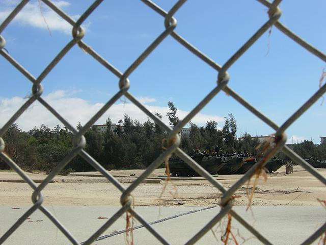 金網の向こうに演習する米軍車両。名護市辺野古のキャンプシュワブで